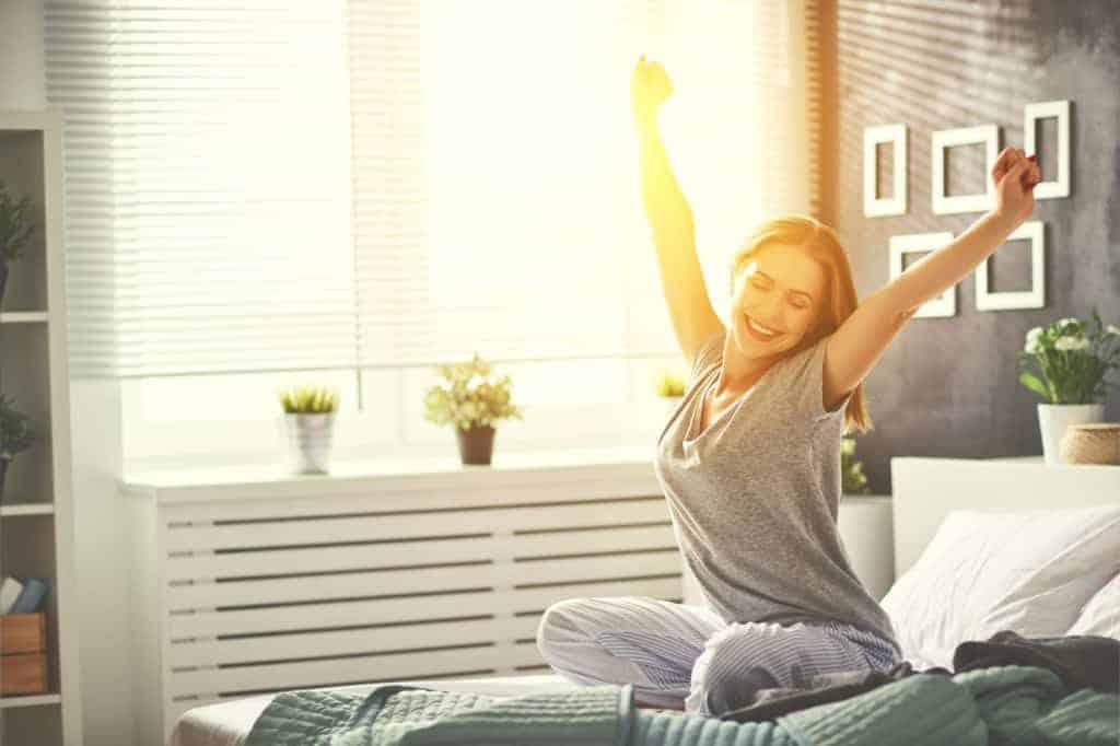 Junge Frau sitzt am Morgen glücklich in Sonnenstrahlen auf dem Bett. (Fensterplanung)