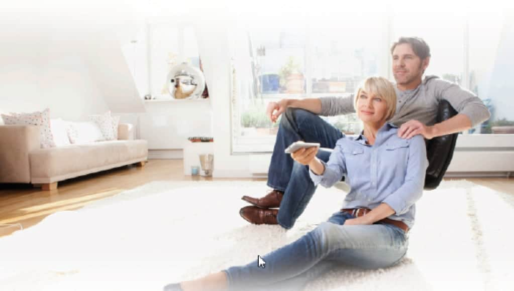 Paar sitzt vor einem großen Fenster. Er im Sessel, sie auf dem hellen Teppich. (Fensterplanung)