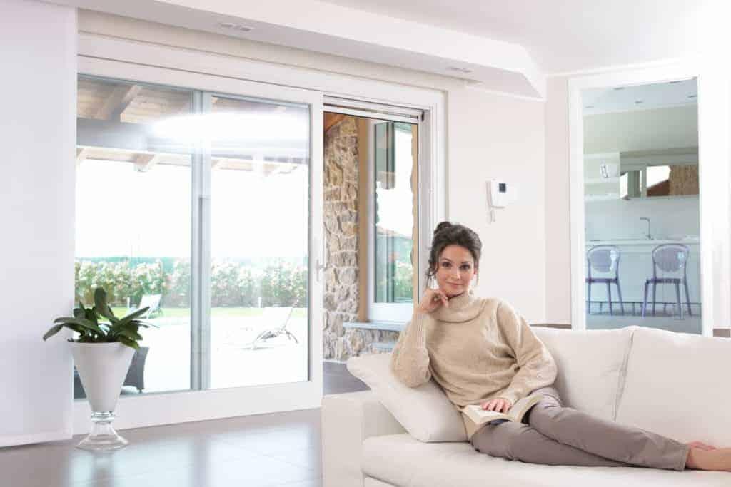 Frau sitzt auf dem Sofa vor der Terrassentür. (Fensterplanung)