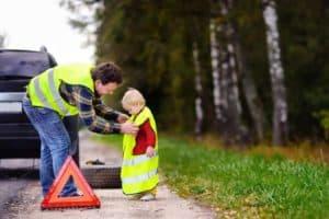 ein Mann steht neben einem Pannenfahrzeug und zieht seinem Sohn eine Sicherheitsweste über.