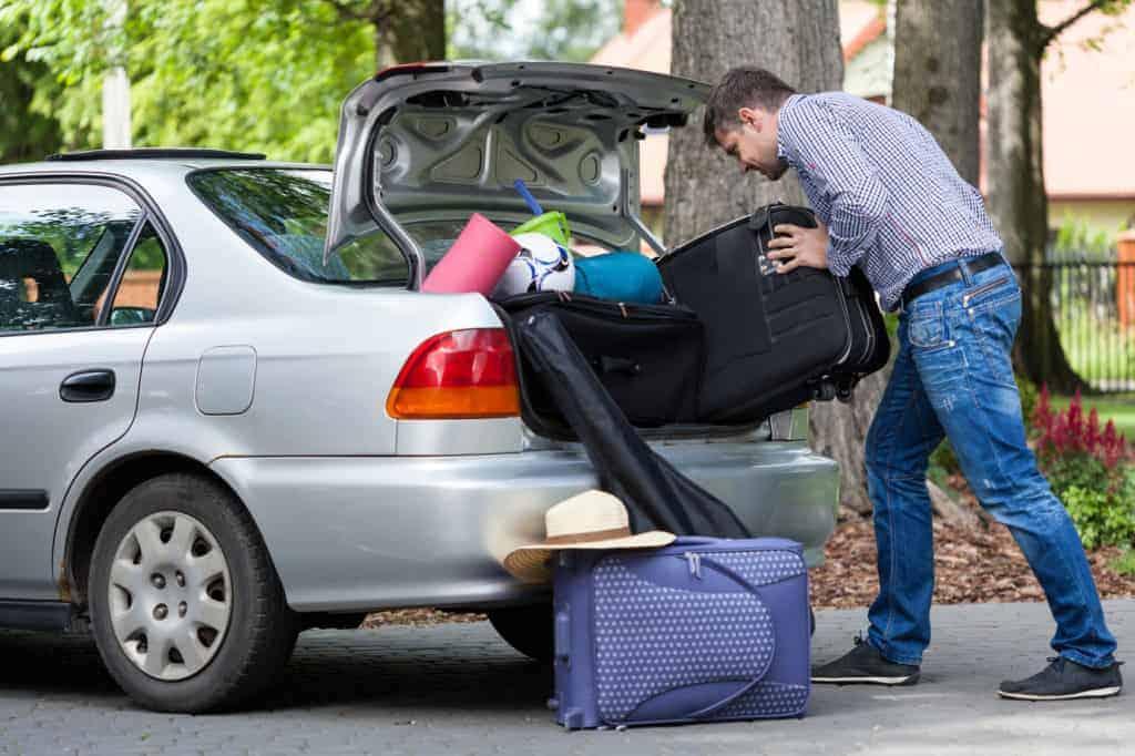 Ein Mann versucht koffer in ein bereits überladenes Auto zu schieben.