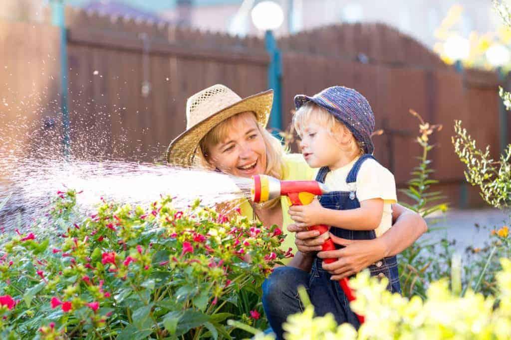 Eine fröhliche Mutter sprengt mit einem Gartenschlauch gemeinsam mit dem Kind das Blumenbeet (Garten bei Trockenheit)