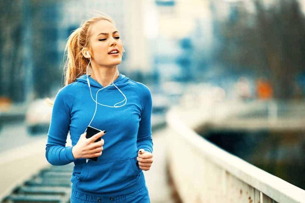 Joggen für Anfänger: Junge Frau im Blauen Trainingsanzug mit Smartphnone und Kopfhörern beim Joggen.