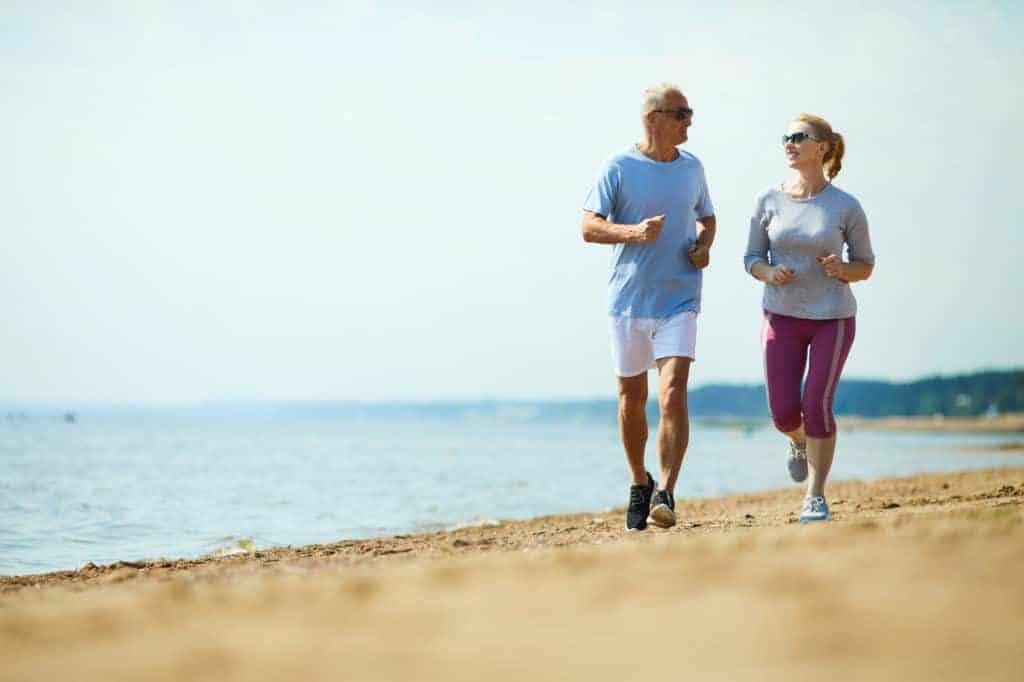 Senior joggt mit Frau am Strand (Joggen für Anfänger)