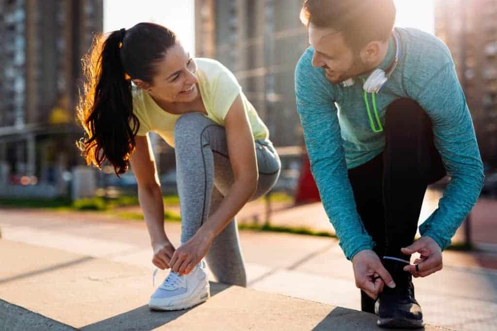 Joggen für Anfänger: junge Joggerin und ihr Trainingspartner binden sich die Schuhe zu.