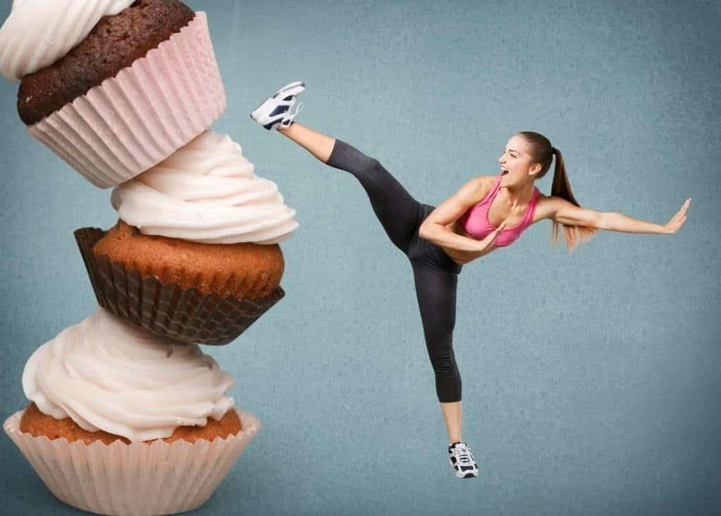 Eine Frau tritt gegen einen überdimmensionalen Turm aus Cupcakes.(Fitness-Mythen)