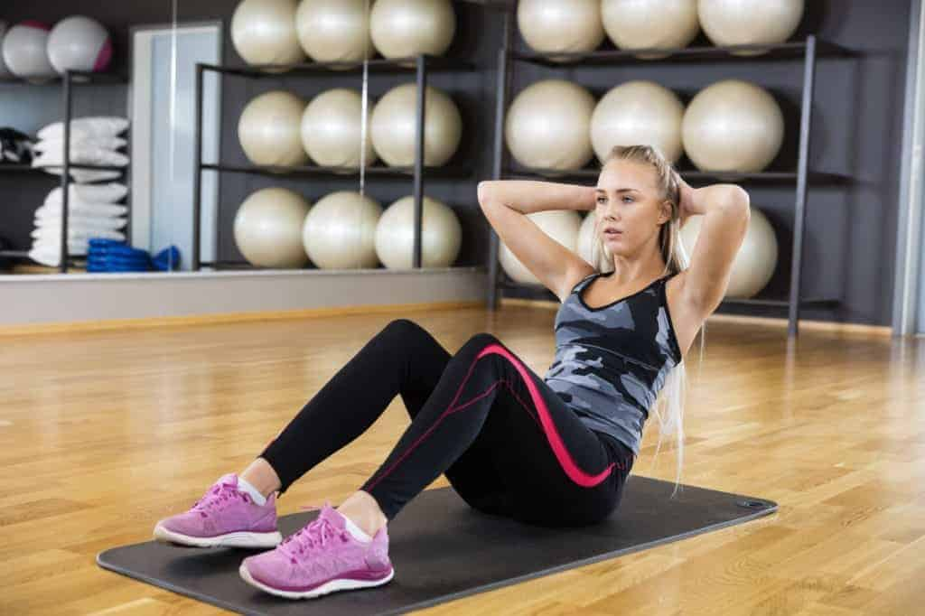 Frau im Fitness-Studio macht Sit-Ups