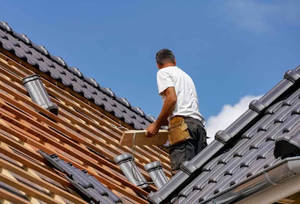 ein Dachdecker verlegt hochwertige Dachziegel. (Dachsanierung)