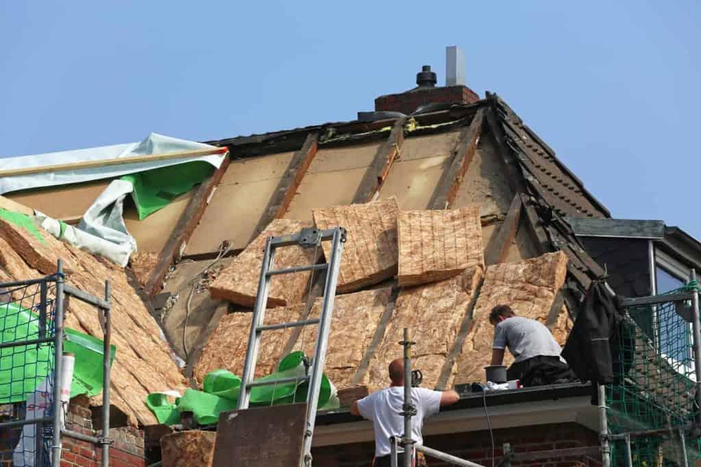 Zwei Handwerker installieren eine neue Wärmedämmung in einem Dach
