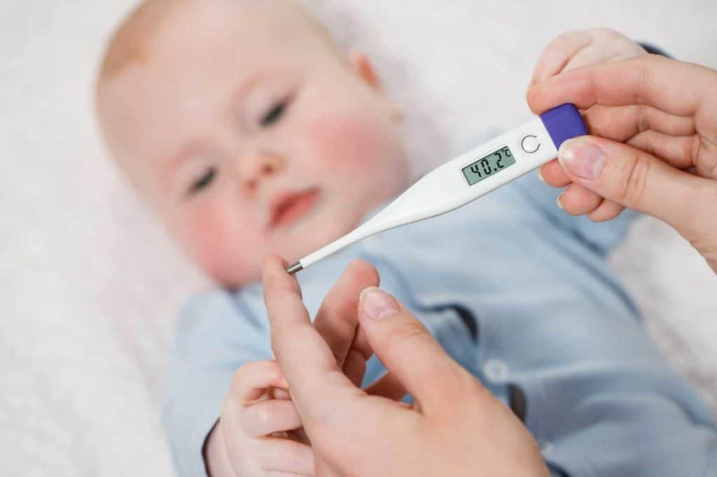 Eine Mutter misst bei ihrem Kind Fieber, welches eine Temperatur von 40,2°C aufweist. (Krankmeldung)