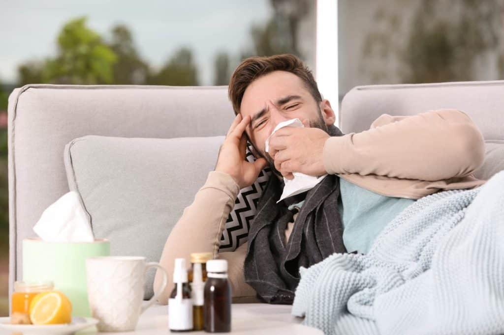 Ein Mann liegt erkrankt auf der Couch. (Krankmeldung)