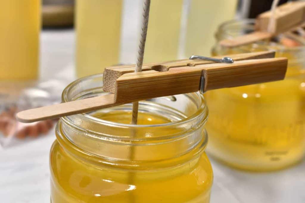 Flüssiges Bienenwachs im Glas mit einem Docht der mit einer Wäscheklammer in den Wachs getaucht wird.