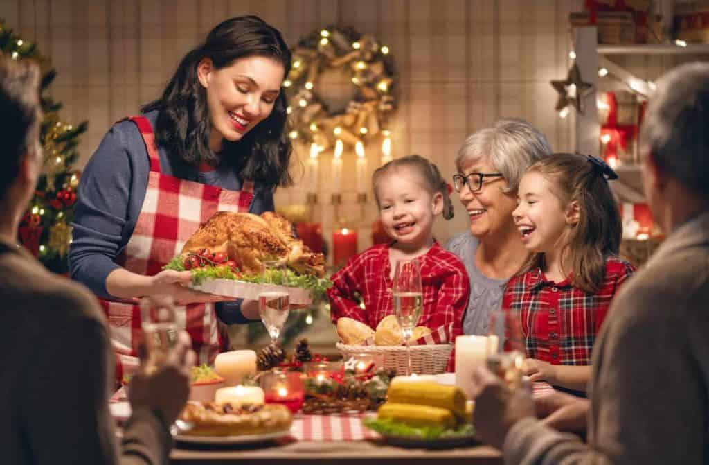 Eine Familie sitzt am weihnachtlich gedeckten Tisch, lachen gemeinsam und freuen sich über das Weihnachtsessen, welches von einer Frau serviert wird. (Weihnachten in anderen Ländern)