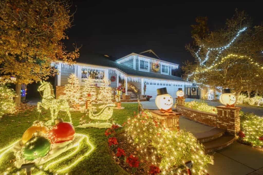 Ein stark geschmücktes und dekoriertes Haus in einer Nachbarschaft. Der Vorgarten ist ebenfalls weihnachtlich geschmückt und stark beleuchtet. (Weihnachten in anderen Ländern)