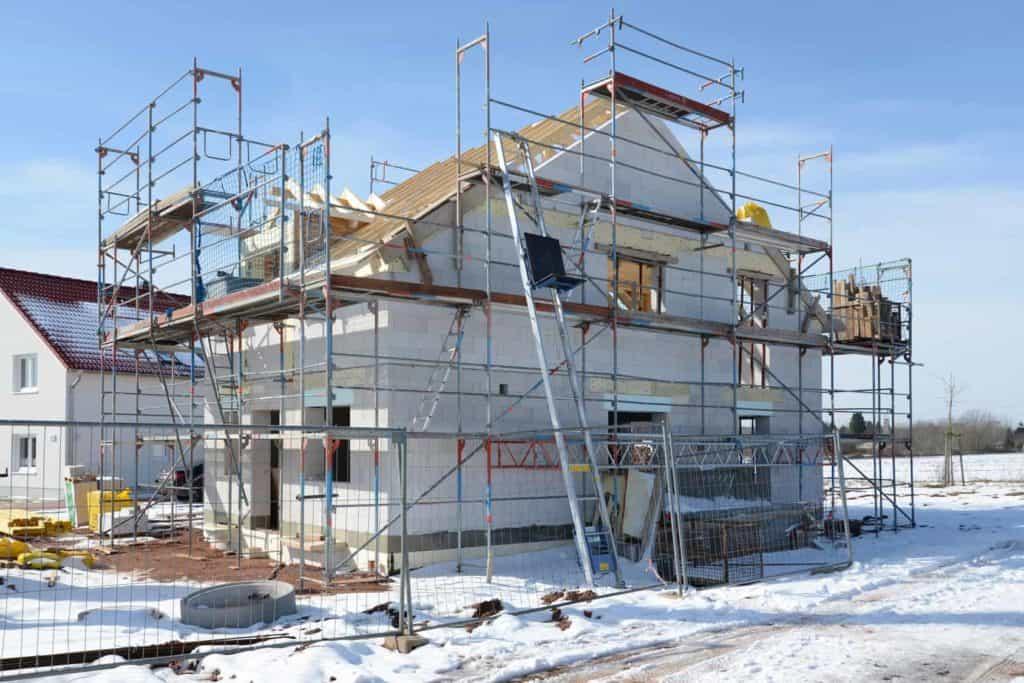Bauen im Winter: Rohbau mit Gerüst im Schnee.