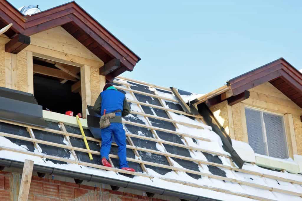 Bauen im Winter: Dachdecker im Schnee auf der Dachkonstruktion.