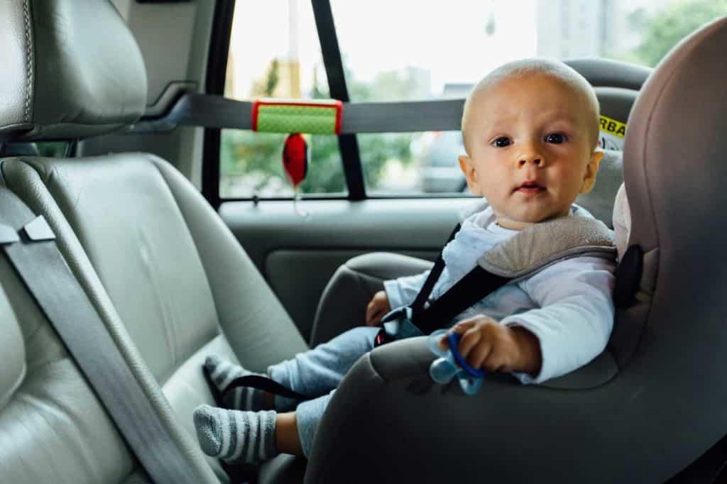 Ein Kleinkindsitzt in einem altergerechten kindersitzt und guckt neugierig in die Kamera. (Autofahren mit Kindern)