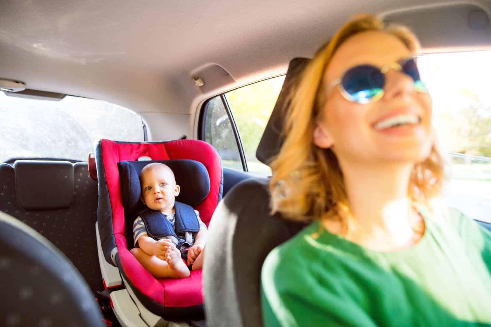 Eine junge Mutter betrachtet während der Fahrt ihr Kind auf der Rückbank durch den Rückspiegel.