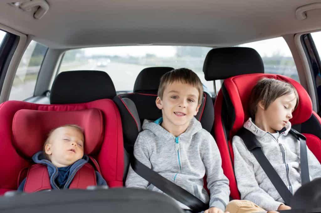 Drei Kinder sitzen auf der Rückbank eines PKWs. Während zwei schlafen, schaut einer aus dem Fenster. (Autofahren mit Kindern)