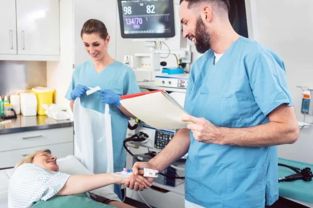 Arzt und Pflegerin begrüßen Patientin im Krankenhaus – Pflegekräfte in der Zeitarbeit
