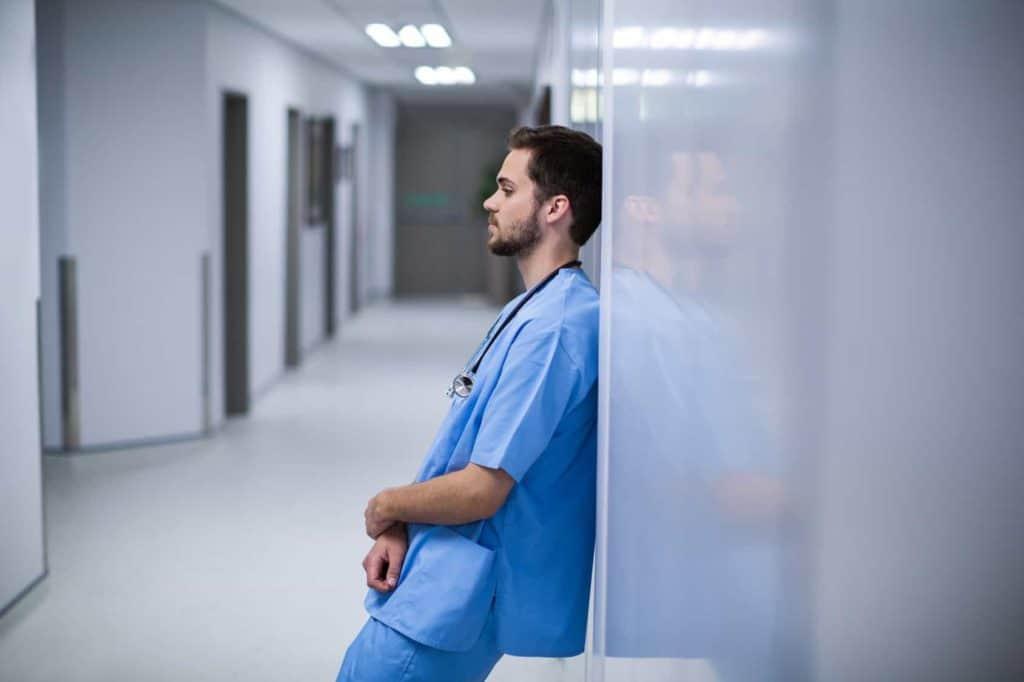 Pfleger lehnt erschöpft an der Wand – Pflegekräfte in der Zeitarbeit