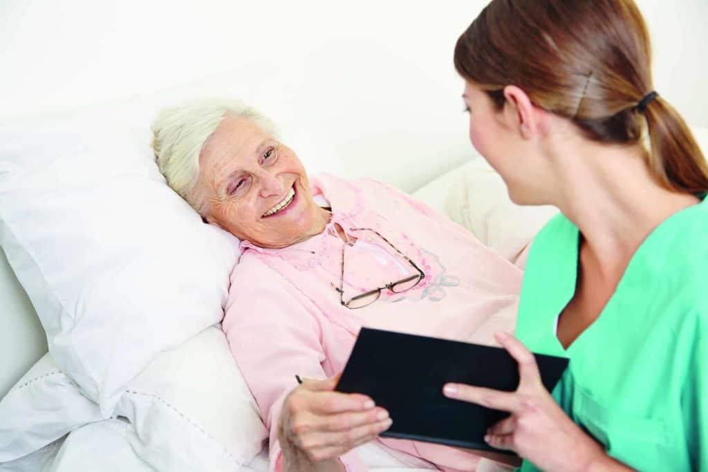 Pflegerin am Bett einer älteren Patientin (Pflegekräfte in der Zeitarbeit)