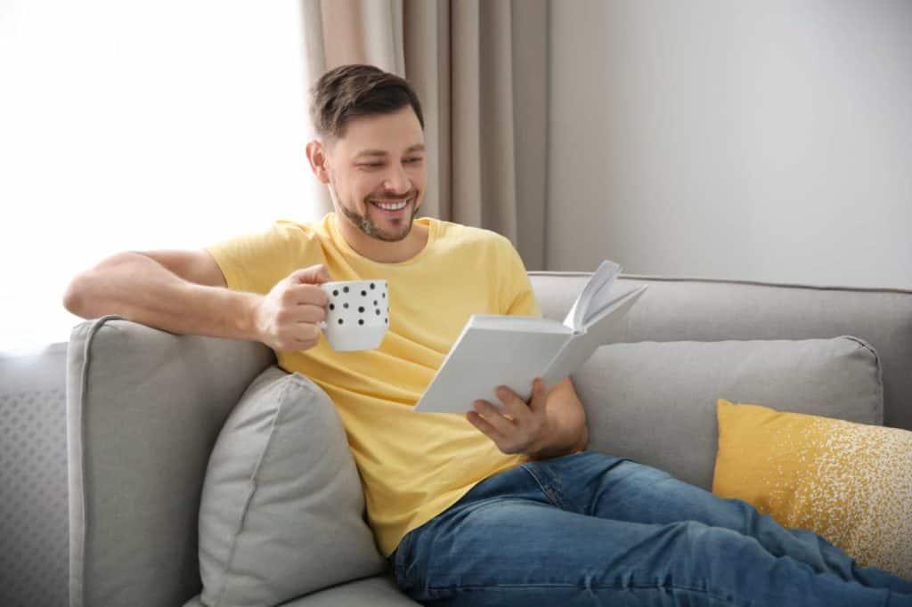 Ein Mann sitzt auf einer Couch, trinkt Tee und liest ein Buch. (Urlaub zuhause)