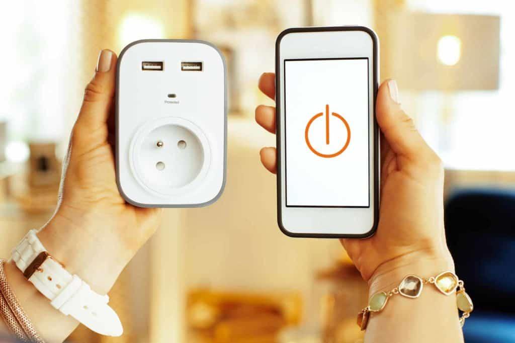 Eine spezielle Steckdose und ein Smartphone mit einer App zum Energiesparen (Energiespartipps)
