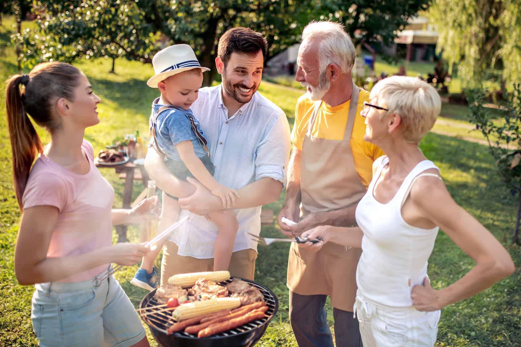 Eine Familie steht gemeinsam um einen Grill und freuen sich (Energiespartipps).