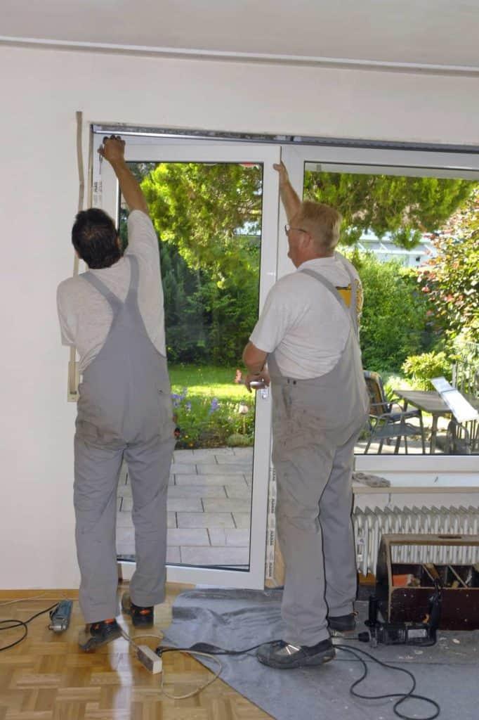 Fenstertausch: Einhängen der neuen Terrassentür durch zwei Handwerker.