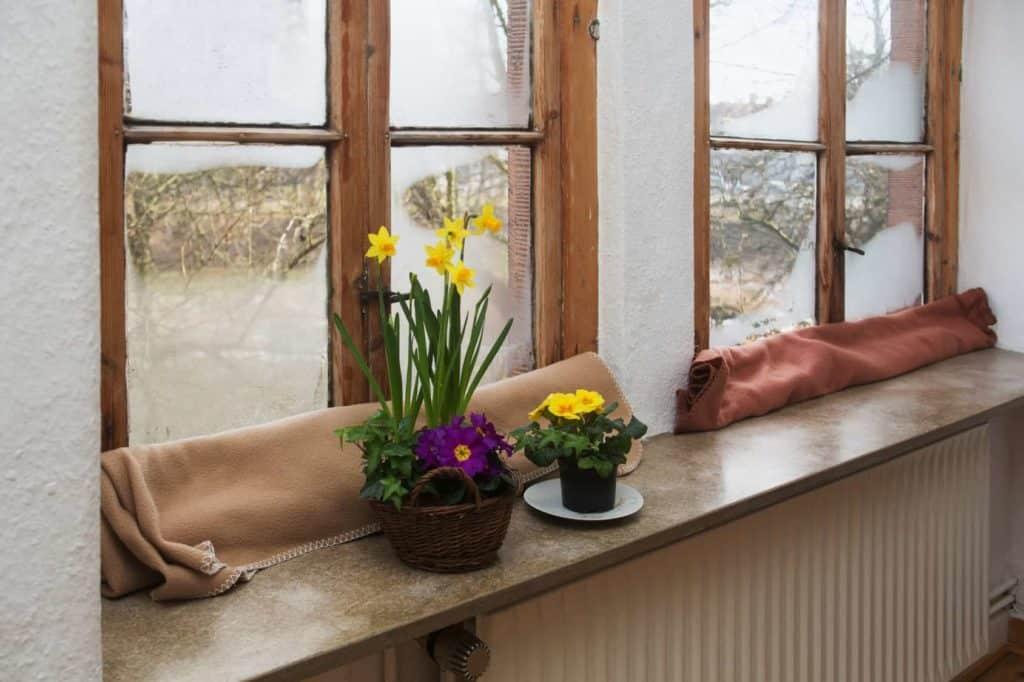 Zeit für den Fenstertausch: altes Fenster mit Wolldecke gegen Zugluft abgedeckt.