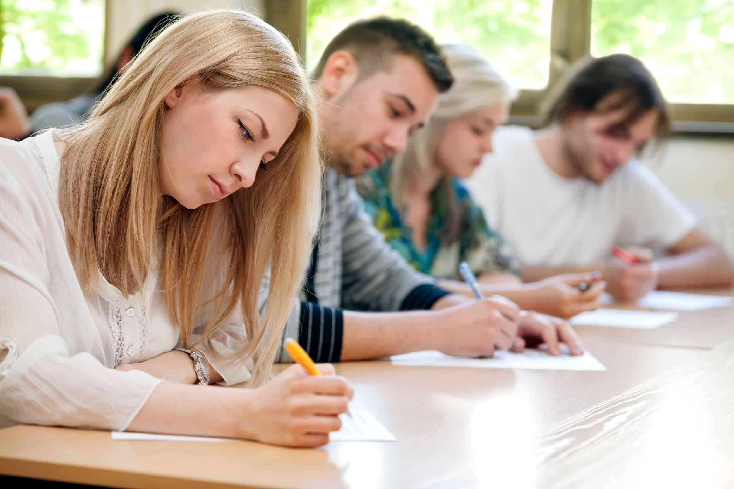 Vier Schüler sitzen nebeneinander und arbeiten (Nach dem Abi).
