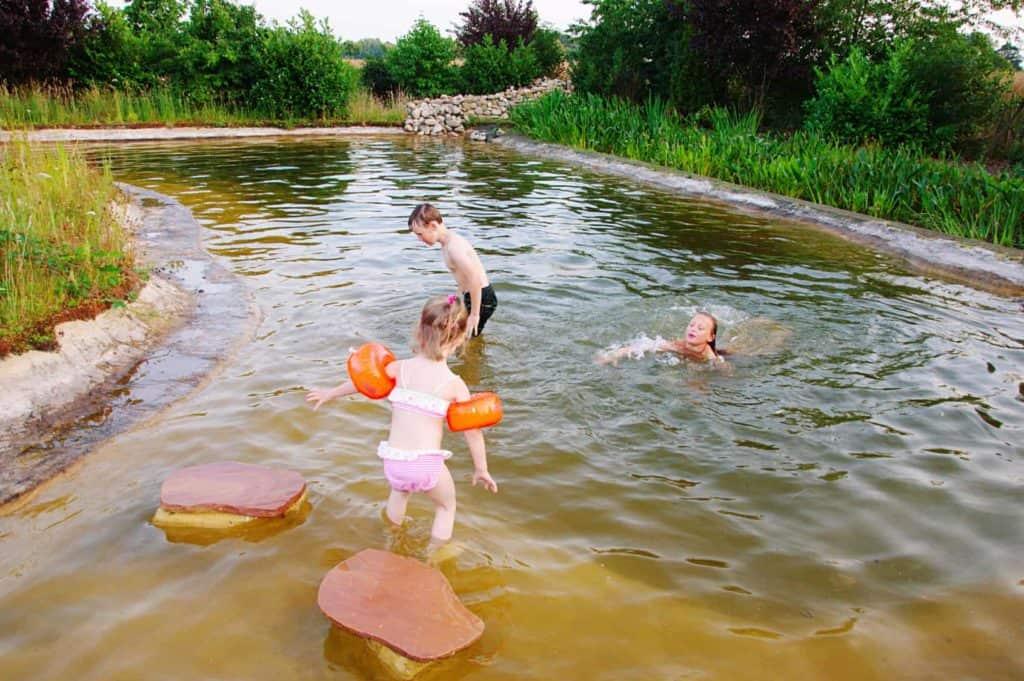 Ein Badeteich mit drei planschenden Kindern. (kindgerechter Garten)