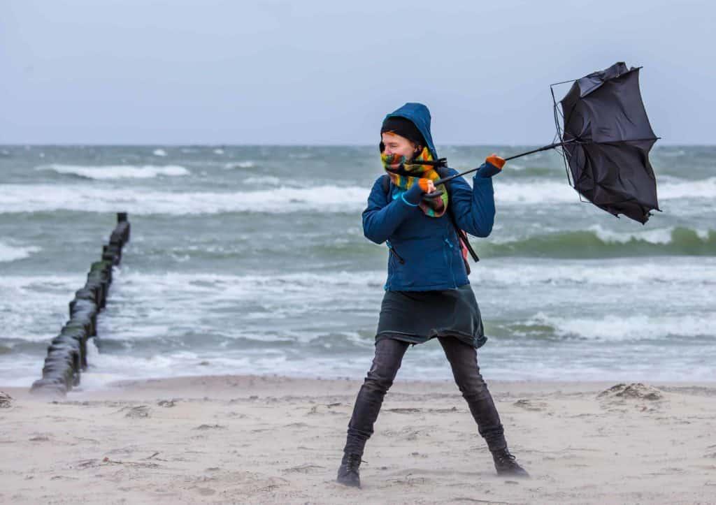 Eine Frau versucht im Sturm einen Regenschirm aufzuspannen. (Fit durch die Herbstzeit)