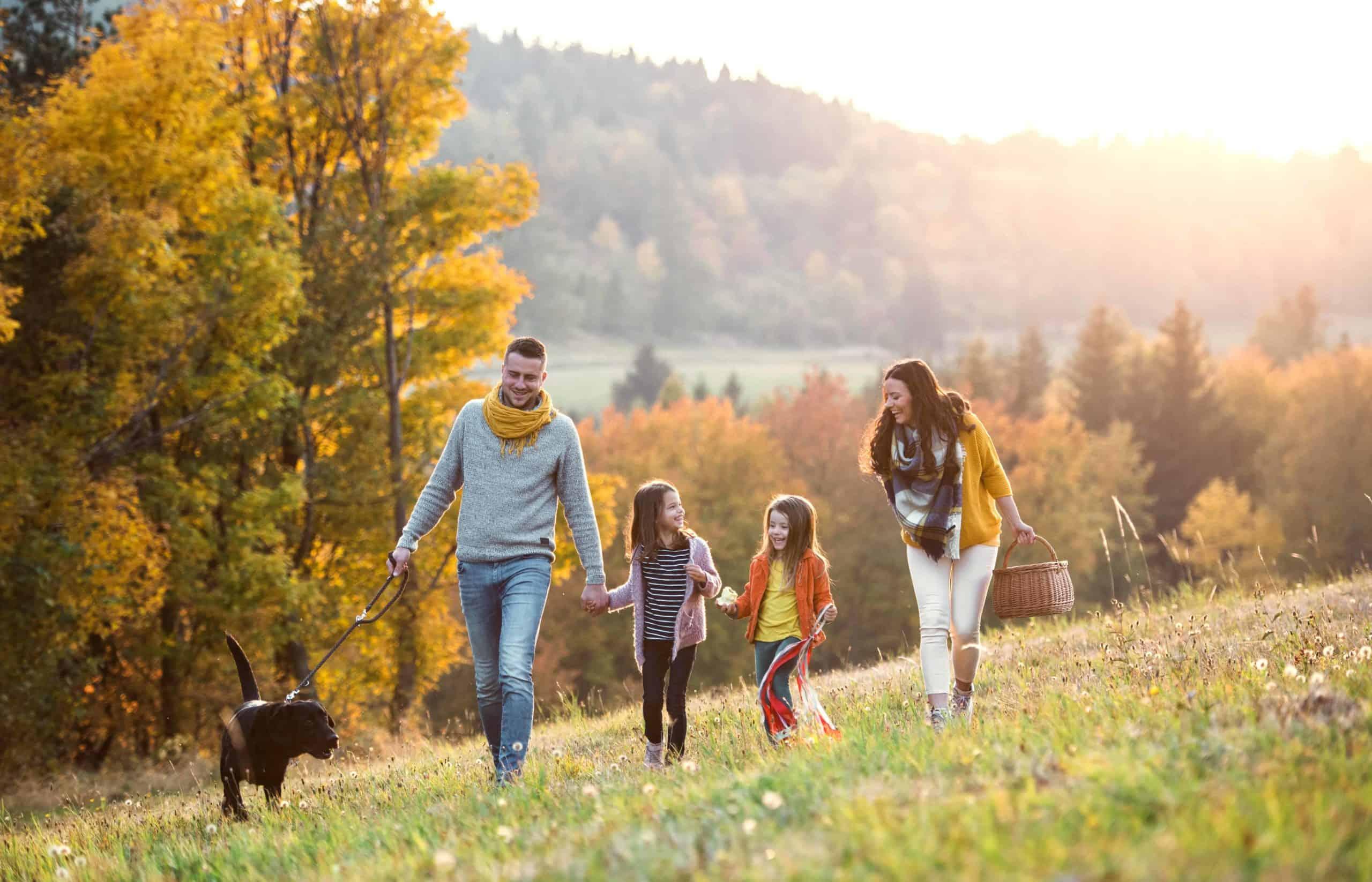 Eine Familie wandert fröhlich durch die Herbstlandschaft.