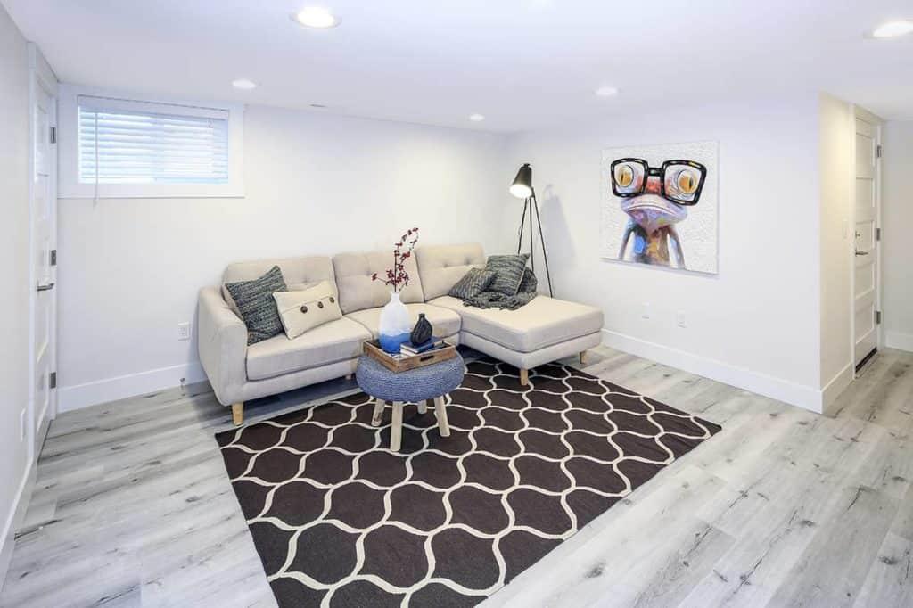 Wohnzimmer mit Sofa, Lampe Tisch und Laminatboden im Kellerraum.
