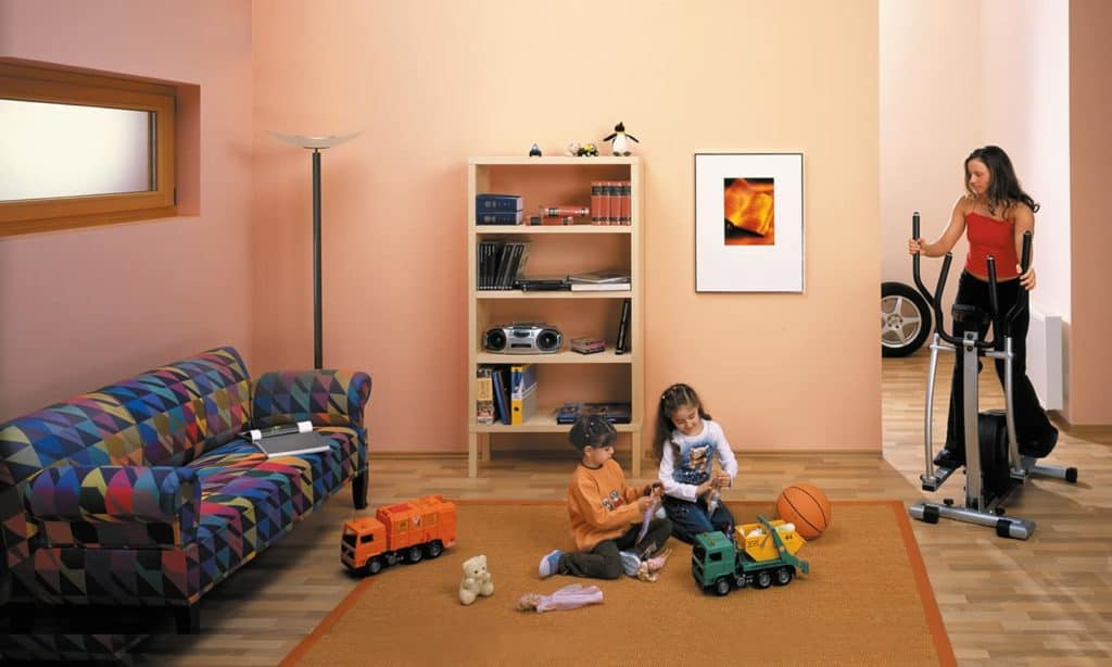 Wohnen im Kellerraum: spielende Kinder vor Sofa und Regal und eine Frau auf dem Stepper.