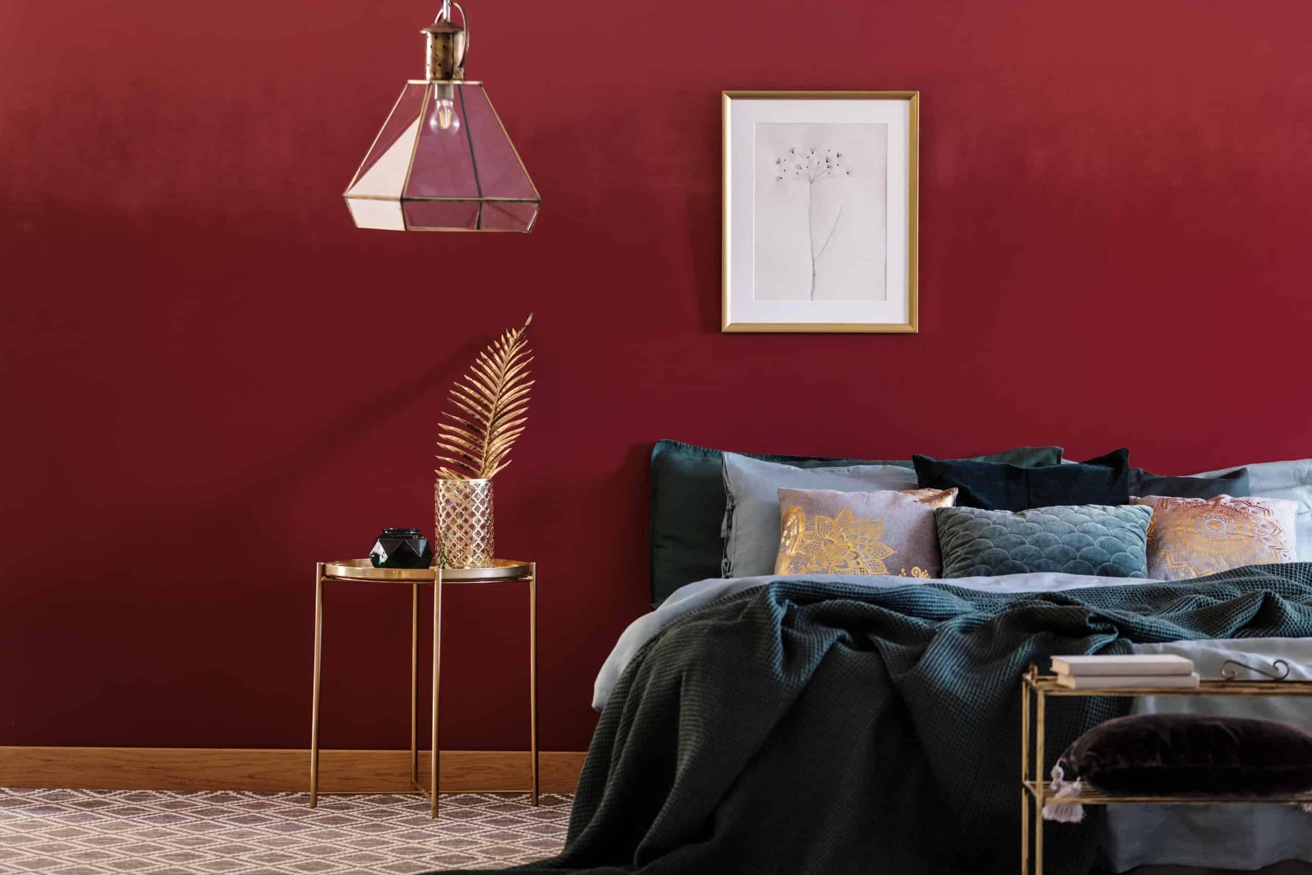 Ein dunkles Bett vor einer Wand in der Trendfarbe bordeaux.