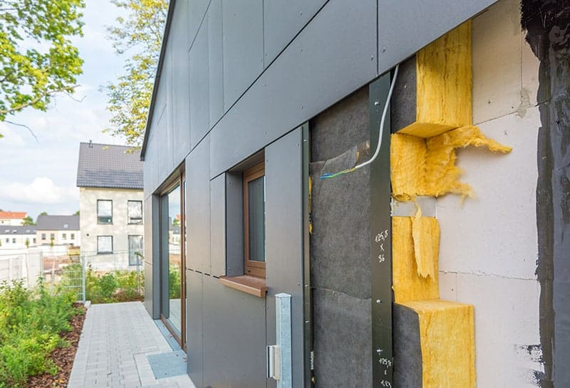 Eine offene Außenwand eines Hauses. Dämmmaterial wird eingesetzt (Dämmen alter Häuser).
