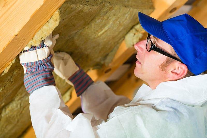 Ein Handwerker verlegt Dämmmaterial an der Innenseite eines Daches (Dämmen alter Häuser).