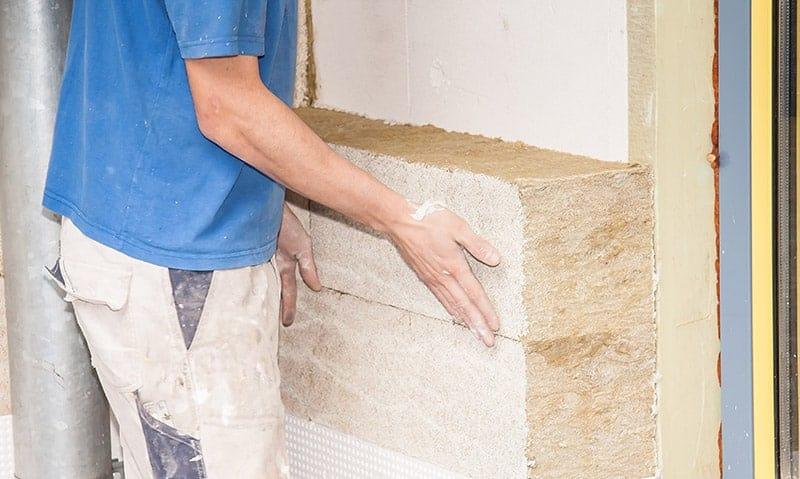 Ein Handwerker verlegt Dämmmaterial an einer Hauswand.