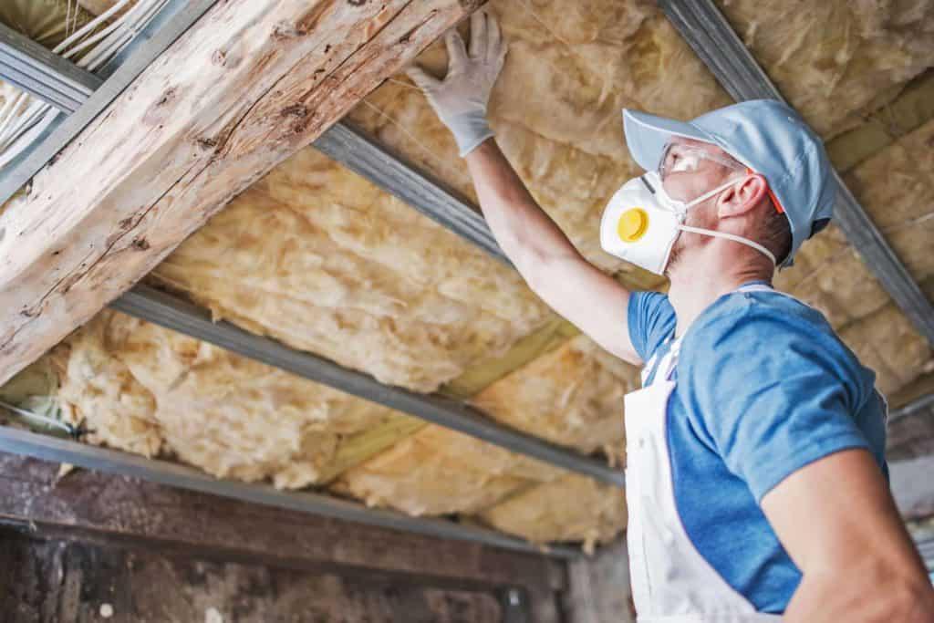 Ein Facharbeiter prüft die Dämmung an der Decke eines Hauses. (Altbausanierung)