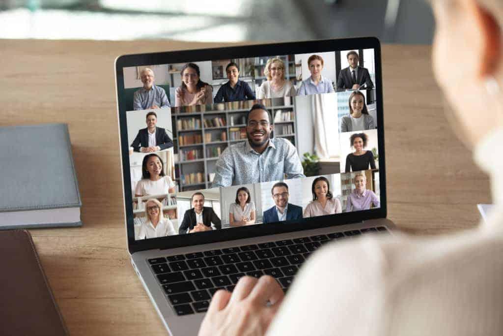 Selbstmanagement im Homeoffice: eine Frau sitzt vor einem offenen Laptop und skypt mit mehreren Leuten.