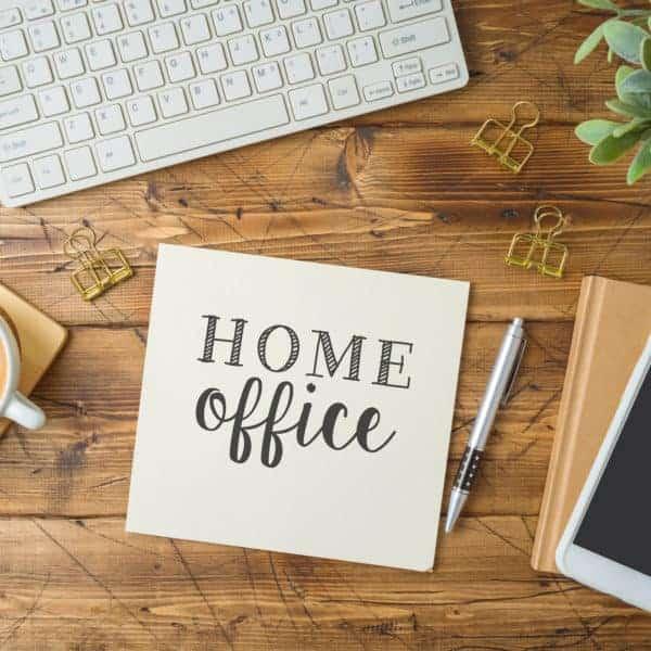 """Ein Schreibtisch mit einem Kaffee, einer Tastatur, einem Handy und einem Notizbuch. Mittig liegt ein Schreibblock mit der Aufschrift """"Homeoffice"""" (Selbstmanagement im Homeoffice)."""
