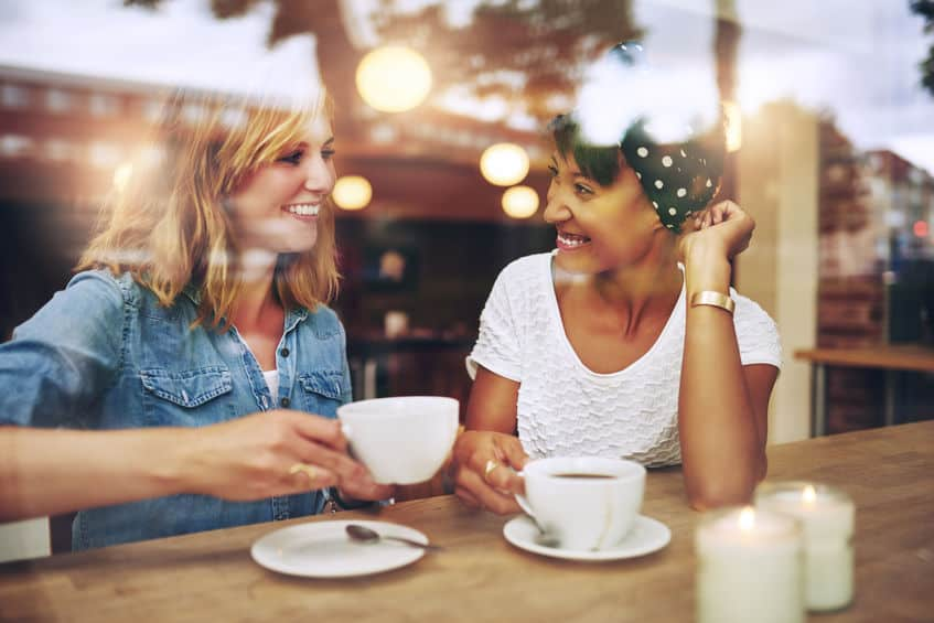 Urlaub daheim: zwei Frauen sitzen nebeneinander, trinken Kaffee und lächeln sich an.