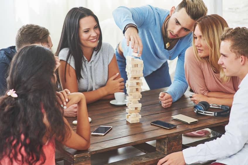 Urlaub daheim: eine Gruppe von sechs jungen Leuten sitzt an einem Tisch und spielt gemeinsam ein Gesellschaftsspiel.