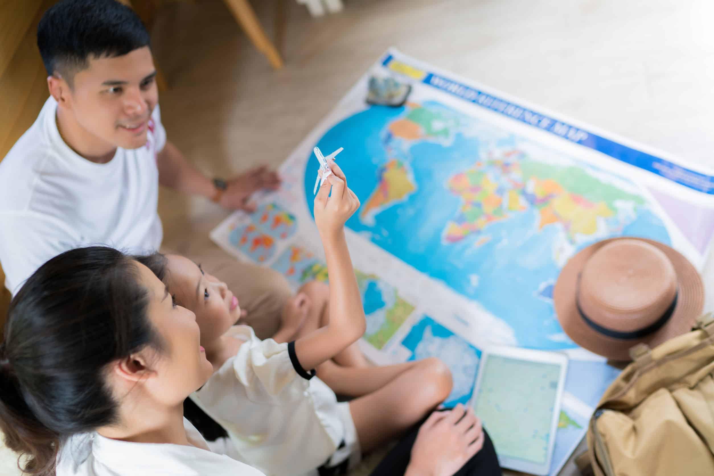 URLaub daheim: eine Familie sitzt zusammen vor einer Weltkarte