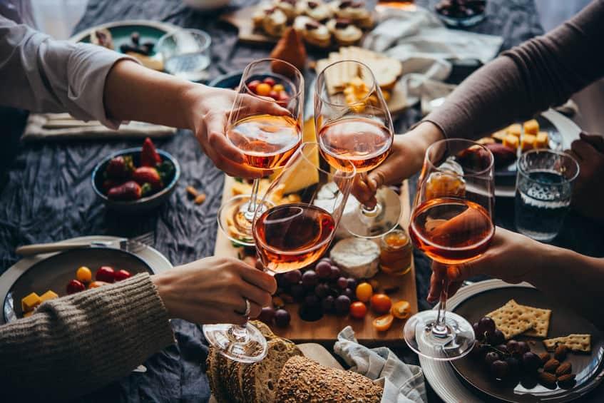 Urlaub daheim: ein reichlich gedeckter Tisch mit Essen. Vier Personen stoßen mit Glasweingläser an.