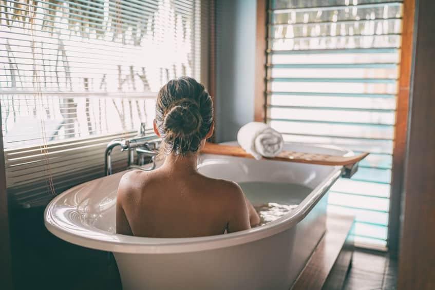 Urlaub daheim: eine Frau liegt in einer mit Wasser befüllten Badewanne und schaut aus dem Fenster.