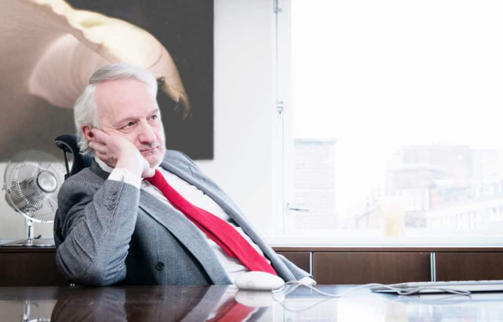Boreout: ein älterer Mann sitzt nachdenklich an einem Schreibtisch und stützt seinen Kopf mit der einen Hand ab.